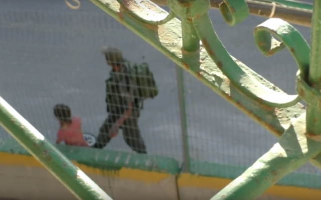 In a video released by the left-wing B'Tselem human rights organization, a Border Police officer appears to pin down an 8-year-old Palestinian girl's bicycle before his comrade takes it and puts it in a nearby bush in Hebron on July 25, 2016. (Screen capture: B'Tselem)