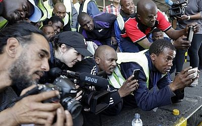 Airport cargo workers and photographers catch a glimpse of tiger Laziz, rescued from a zoo in Gaza, upon its arrival at O.R Tambo international airport in Johannesburg, South Africa, Thursday, Aug. 25, 2016. AP Photo/Themba Hadebe