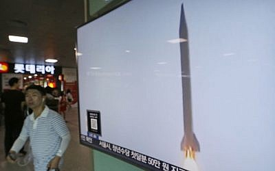 A man passes by a TV news program with file footage of a North Korean rocket launch at the Seoul Railway Station in Seoul, South Korea, August 3, 2016. (AP/Ahn Young-joon)
