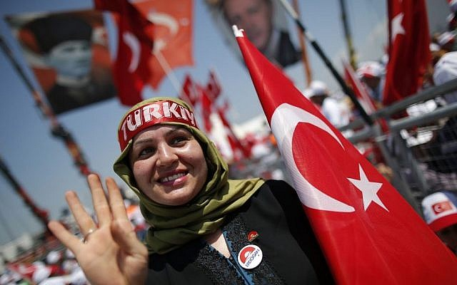 A Turkish woman waves as she holds her country's flag, during a Democracy and Martyrs' Rally in Istanbul, Sunday, Aug. 7, 2016. (AP Photo/Emrah Gurel)