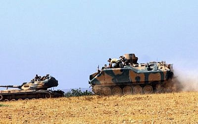 A Turkish army tank and an armored vehicle are stationed near the border with Syria, in Karkamis, Turkey, Tuesday, Aug. 23, 2016. (IHA via AP)