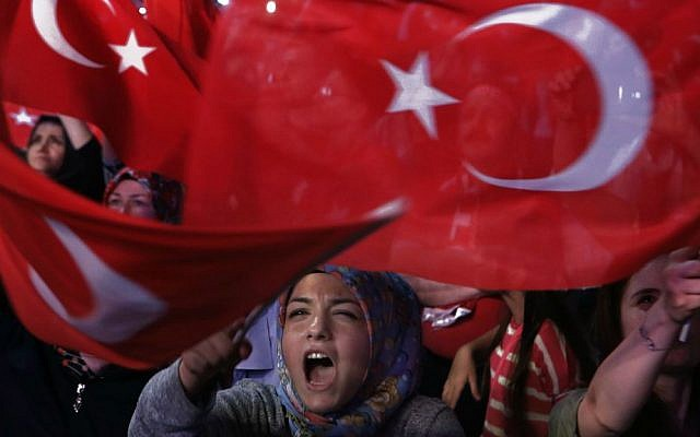 A crowd brandish national flags and shout shouts slogans during a July 25, 2016 anti-coup rally in Istanbul, as a nationalistic fervor engulfs Turkey following the failed military coup attempt. (AP Photo/Petros Karadjias, FILE)