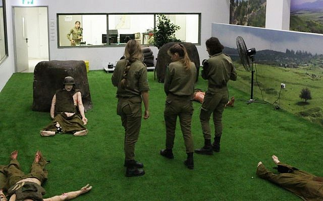 Instructors of the Medical Trauma Simulator prepare for an exercise in the multiple casualty event room. They can monitor the action from the floor or from the viewing room in back. (Luke Tress/Times of Israel)