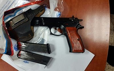 A pistol, two magazines and a carrying case found by police in the bedroom of a 13-year-old resident of East Jerusalem at the educational institution where he lives, on August 2016. (Israel Police)