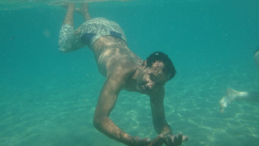 Salman Areb, 38, the accountant and kitchen manager at the Big Dune Camp, takes a swim on August 15, 2016 (courtesy Yuval Saidman).