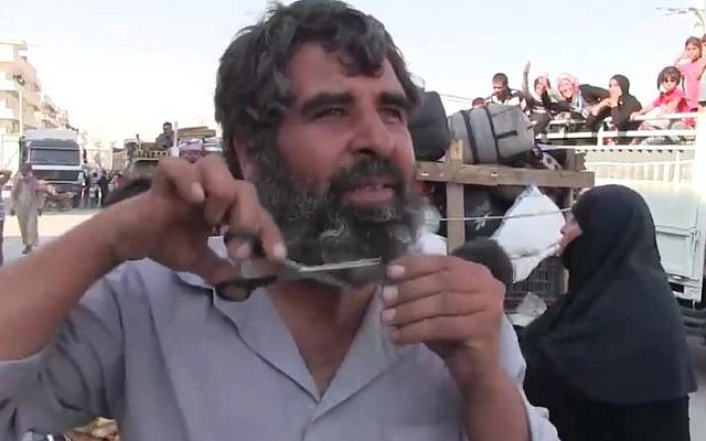 A Syrian man clips his beard after his town of Manbij was freed from Islamic State control, August 13, 2016. (Screenshot/K24)