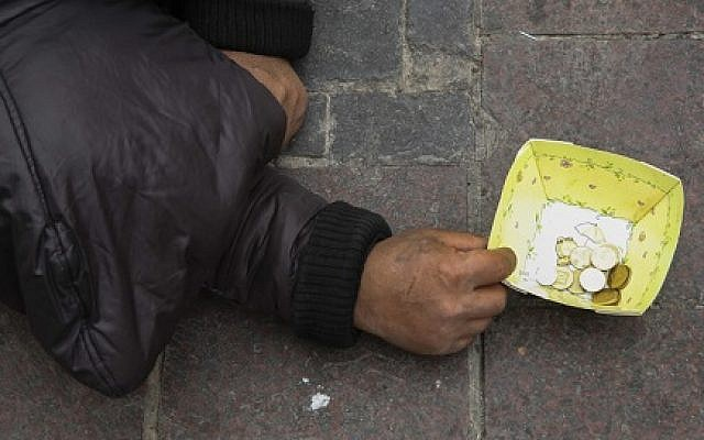 illustrative: A man asks for money on the streets in the center of Jerusalem, March 17, 2014. (Nati Shohat/Flash90)