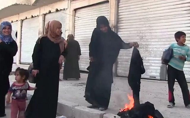 A Syrian woman burning a burqa in celebration of the freeing of the town of Manbij from IS control, August 13, 2016. (Screenshot/K24)
