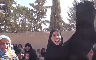 A woman burns a full-body covering in the street as residents celebrate the retreat of Islamic State in Manbij, Syria, August 2016 (YouTube screenshot)