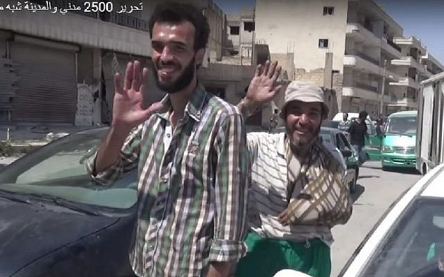 Syrian civilians wave as the town of Manjib is freed from IS control by US-backed coalition forces, August 12, 2016. (Screenshot/Anha)