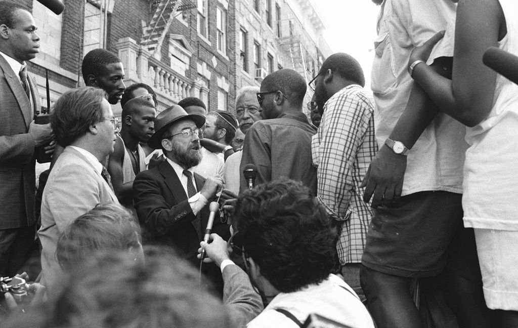 New York City Mayor David Dinkins, fourth from right, looking on while a Hasidic Jew and a black man argue during riots in Crown Heights, Brooklyn, in 1991. (Anthony Pescatore/NY Daily News Archive via Getty Images/via JTA)