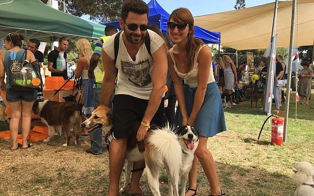 Hod Kashtan, left, with his dog Chuni, and Florencia Aventuriny with her dog Sandy at the Kelaviv dog festival in Tel Aviv, Aug. 26, 2016. (Andrew Tobin/JTA)