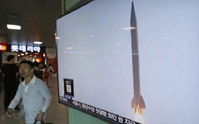 A man passes by a TV news program with  file footage of a North Korean rocket launch at the Seoul Railway Station in Seoul, South Korea, Wednesday, Aug. 3, 2016. (AP Photo/Ahn Young-joon)