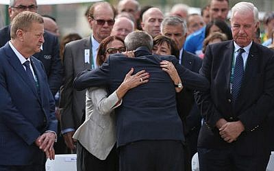 IOC President Thomas Bach embraces Ilana Romano, right, and Ankie Spitzer, widows of Israeli Olympic athletes killed by Palestinian gunmen at the 1972 Munich Olympics, during the inauguration of a memorial in their husbands' honor, ahead of the Summer Olympics in Rio de Janeiro, Brazil, Wednesday, Aug. 3, 2016. (AP Photo/Edgard Garrido, Pool)