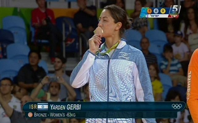 Israeli judoka Yarden Gerbi kisses her bronze medal for the women's under-63kg category during the awards ceremony at the Olympic Games in Rio on August 9, 2016 (screen capture: Channel 55)