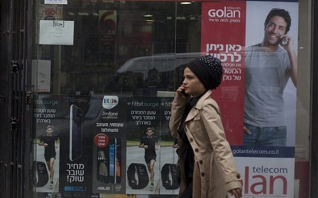 A woman walks next to an advertisement  for Golan Telecom in Jerusalem on November 05, 2015. Photo by Lior Mizrahi/Flash90
