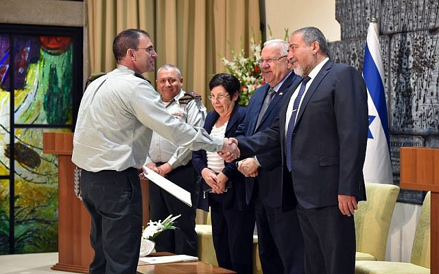 Maj. Gen. Doron Piles (left) shakes hands with Defense Minister Avigdor Liberman as he receives his appointment as the new president of the IDF's Military Court of Appeals, during a ceremony at the President's Residence attended by President Reuven Rivlin, President of the Supreme Court Miriam Naor and IDF Chief of Staff Gadi Eisenkot on August 15, 2016. (Ariel Hermoni/Defense Ministry)