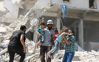 Syrian civilians and a rescue worker evacuate children in the Maadi district of eastern Aleppo after regime aircraft reportedly dropped explosive-packed barrel bombs, August 27, 2016. (AFP/Ameer Alhalbi)