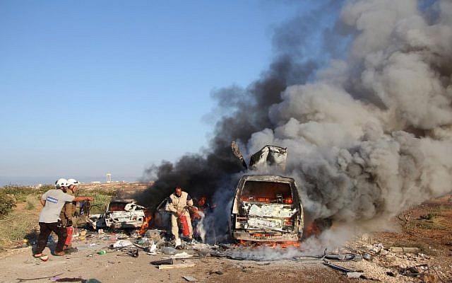 Syrian Civil Defense members, known as the White Helmets, search for survivors amid burning vehicles belonging to people fleeing in northern Hama, after they were reportedly targeted by a Syrian government forces air strike on September 1, 2016. (AFP Photo/Omar Haj Kadour)