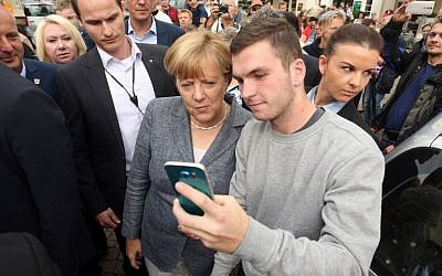 German Chancellor Angela Merkel poses for a selfie with a young man at a Christian Democratic Union  party campaign on the eve of state election in Mecklenburg-Western Pomerania, in Bad Doberan, eastern Germany, on September 3, 2016. (AFP / Adam BERRY)