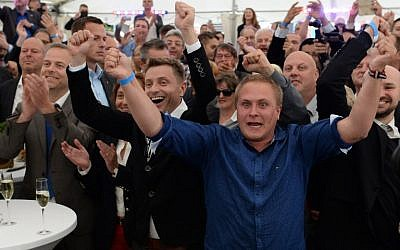 Supporters of the anti-migrant populists AfD react as exit polls were announced on TV during an election results party on September 4, 2016 in Schwerin, north-eastern Germany. (AFP PHOTO / dpa / Daniel Bockwoldt).