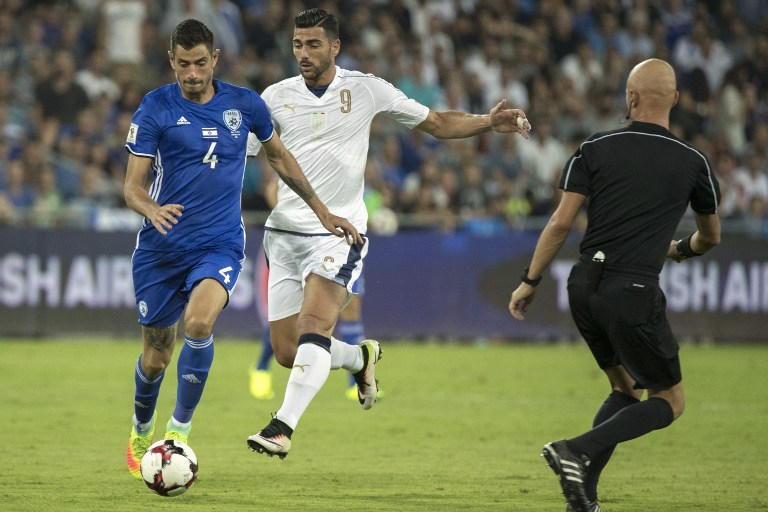 Israel's midfielder Nir Biton (L) evades Italy's forward Graziano Pelle during the World Cup 2018 qualifying football match between Israel and Italy at Sammy Ofer Stadium in Haifa on September 5, 2016. (AFP PHOTO / JACK GUEZ)