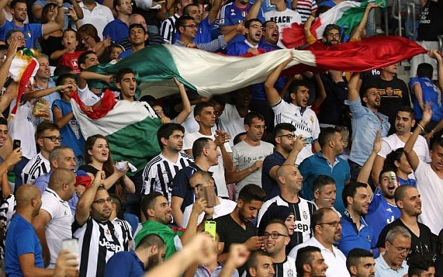 Illustrative: Italian fans celebrate after Italy scored their third goal during the World Cup 2018 qualifying football match between Israel and Italy at Sammy Ofer Stadium in Haifa on September 5, 2016. (AFP/Menahem Kahana)