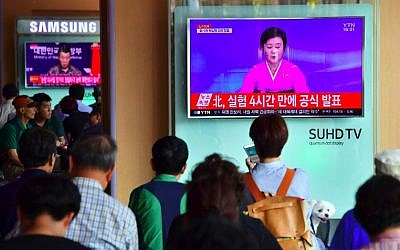 People watch a television news broadcast showing a North Korean anchor announcing the country's latest nuclear test, at a railway station in Seoul on September 9, 2016. (AFP  Jung Yeon-Je)