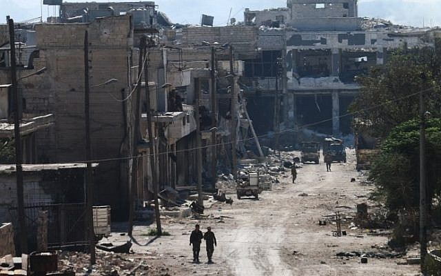 Syrian pro-regime fighters walk in a bombed-out street in Ramussa on September 9, 2016, after they took control of the strategically important district on the outskirts of the Syrian city of Aleppo a day earlier. (AFP/ GEORGE OURFALIAN)