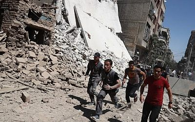 Syrians run for cover during reported government air strikes in the rebel-held town of Douma, east of the capital Damascus, on September 9, 2016. (Abd Doumany / AFP)