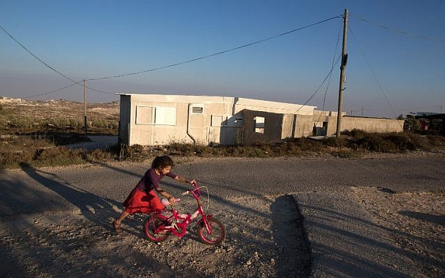 An Israeli girl walks with her bicycle near her home in the wildcat Amona settlement, northeast of the Palestinian city of Ramallah in the Israeli occupied West Bank, on September 7, 2016. An Israeli court has ruled that the wildcat Jewish settlement of Amona, where Ziv lives alongside around 40 other families in mainly caravan homes, is on Palestinian property and must be evacuated by December 25. Settlements such as Amona are called outposts -- those that Israel has not approved. Outpost residents hope such authorisation will one day be provided, as has occurred in other cases. Amona, one of the largest outposts with between 200 and 300 people, has come to represent a list of issues at the heart of the Israeli-Palestinian conflict. (AFP PHOTO / MENAHEM KAHANA)