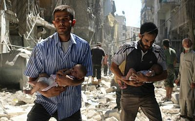 Syrian men carrying babies make their way through the rubble of destroyed buildings following a reported air strike on the rebel-held Salihin neighborhood of the northern city of Aleppo, on September 11, 2016. (Ameer Alhalbi/AFP)