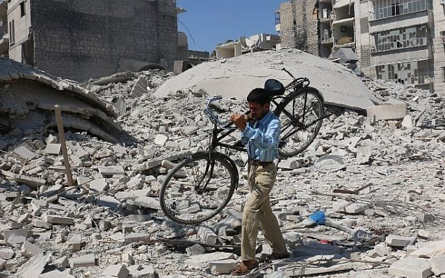 A Syrian man carrying a bicycle makes his way through the rubble of destroyed buildings following a reported air strike on the rebel-held Salihin neighbourhood of the northern city of Aleppo, on September 11, 2016. (AFP PHOTO / AMEER ALHALBI)