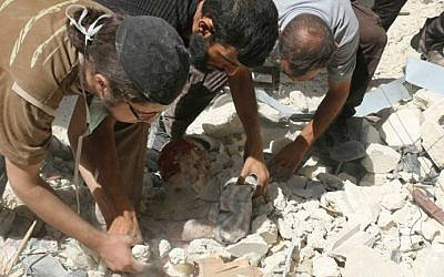 Syrian men remove a victim from under the rubble of destroyed buildings following a reported air strike on the rebel-held Salihin neighborhood of the northern city of Aleppo, on September 11, 2016. (Ameer Alhalbi/AFP)