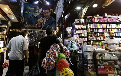 "A poster of the Syrian President Bashar al-Assad and reading in Arabic: "" Assad is with you forever"" hangs above Syrians shopping at the Hamidiyeh popular market in the old part of the capital Damascus as they prepare for the Muslim Eid al-Adha holiday on September 11, 2016. (AFP PHOTO / LOUAI BESHARA)/"