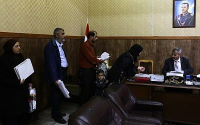 Syrians queue up in the office of Judge Mahmoud Al-Maarawi (R), who heads the religious court that oversees personal status issues for Syria's Sunni Muslims, to get official documents related to their marital affairs, such as legal papers for divorce or for second marriages in Damascus, March 8, 2016. (AFP PHOTO / LOUAI BESHARA)