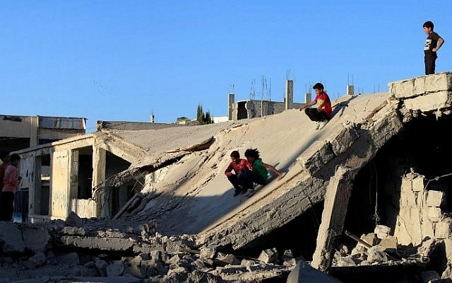 Syrian children slide down rubble of destroyed a building in the rebel-held city of Daraa, in southwestern Syria on September 12, 2016 (AFP PHOTO / MOHAMAD ABAZEED)