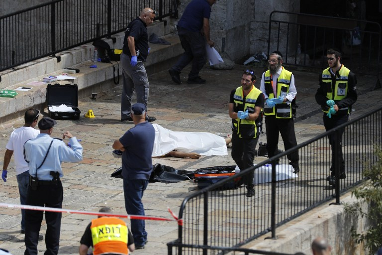 Israeli forensic policemen gather around the body of a Jordanian assailant who was shot dead following a reported attack at the entrance to the Old City of Jerusalem on September 16, 2016.(AFP PHOTO / Thomas COEX)