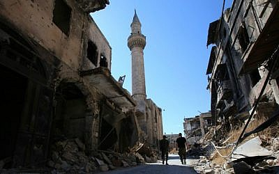 Syrian government soldiers walk in the damaged al-Farafira souk in the government-held side of Aleppo's historic city center on September 16, 2016. (Youssef Karwashan/AFP)