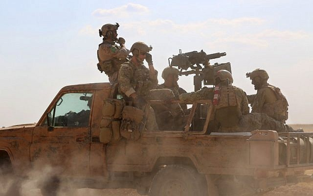 This file photo taken on May 25, 2016 shows armed men in uniform identified by Syrian Democratic forces as US special operations forces riding in the back of a pickup truck in the village of Fatisah in the northern Syrian province of Raqqa. (AFP/Delil Souleiman)
