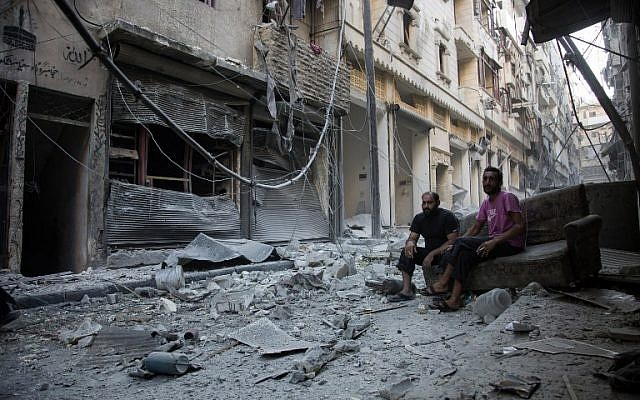 Syrians sit and look at the rubble following an air strike in Aleppo's rebel-controlled neighborhood of Karm al-Jabal, September 18, 2016. (AFP/Karam al-Masri)