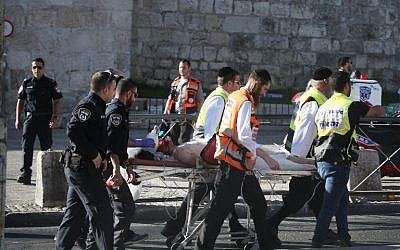 Israeli medics carry an injured man following a Palestinian stabbing attack outside the Old City of Jerusalem, on September 19, 2016 (AFP PHOTO / MENAHEM KAHANA)