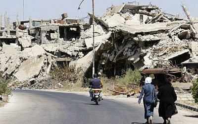 Syrians walk and drive past destroyed buildings in the government held Jouret al-Shiah neighbourhood of the central Syrian city of Homs on September 19, 2016. (AFP PHOTO/LOUAI BESHARA)