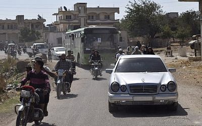 A bus carrying opposition fighters and their families drives through the rebel-held Waer neighbourhood in the central city of Homs as it heads to a Syrian army checkpoint during an evacuation operation on September 22, 2016. (AFP / MAHMOUD TAHA)
