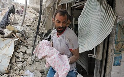 A Syrian man carries the body of an infant retrieved from under the rubble of a building following a reported airstrike on September 23, 2016, on the al-Muasalat area in the northern Syrian city of Aleppo. (AFP PHOTO/THAER MOHAMMED)