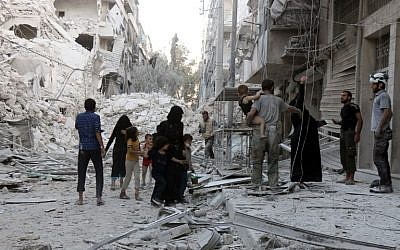 A Syrian family leaves the area following a reported airstrike on September 23, 2016, on the al-Muasalat area in the northern city of Aleppo. (AFP/Thaer Mohammed)