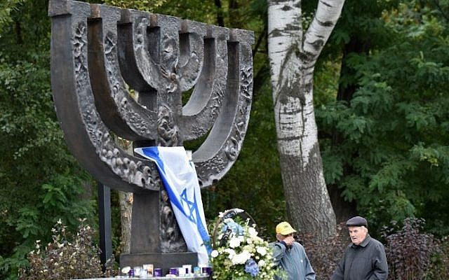 Men react during a visit to the Babi Yar menorah monument in Kiev on September 23, 2016. (AFP Photo/ Sergei Supinsky)