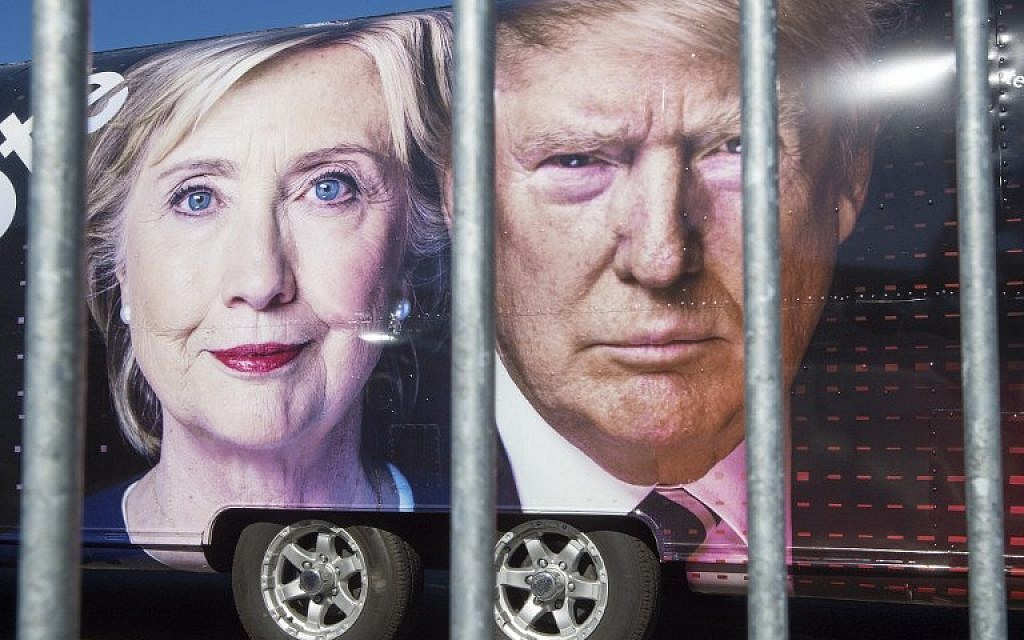 Large images of Democratic nominee Hillary Clinton and Republican nominee Donald Trump are seen on a CNN vehicle, behind a security fence, on September 24, 2014, at Hofstra University, in Hempsted, New York. (AFP/ PAUL J. RICHARDS)