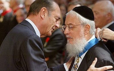 French President Jacques Chirac (L) hugging France's Chief Rabbi Joseph Sitruk, after honoring him with the medal of Commander of the National Order of Merit during a ceremony at the Elysee Palace in Paris, July 7, 2003 (Patrick Kovarik/AFP)    Joseph Sitruk, who acted as Chief Rabbi of France for over 20 years, died on September 25, 2016 in Paris at the age of 71, the entourage of his successor Haim Korsia said. / AFP PHOTO / PATRICK KOVARIK