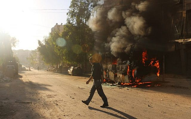 A Syrian man walks past a bus set ablaze following a reported air strike in the rebel-held Salaheddin district of Aleppo on September 25, 2016. (AFP/Ameer Alhalbi)
